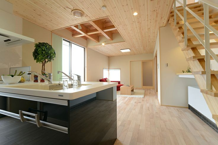 T-N house:ホワイトと木肌の色合いの中に濃いグリーンのアイランドキッチンと赤のソファーが差し色になっています。