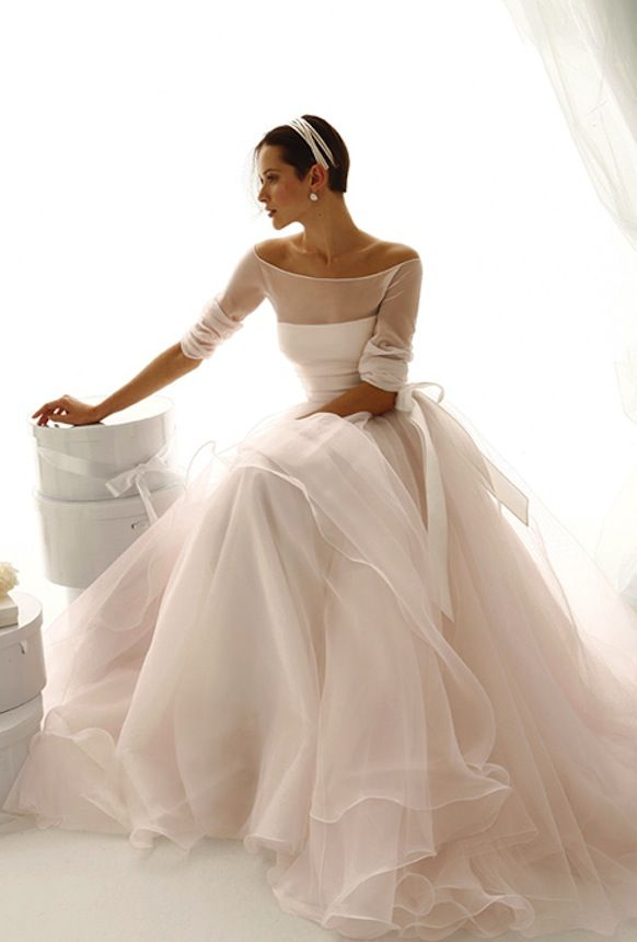This graceful boatneck design by Le Spose di Gio is sure to make any bride look radiant. The airy and delicate neckline evoke old vintage glamour  and the sheer sleeves add a graceful touch. We can only imagine how the light, full, and dreamy skirt of sheer chiffon will look as you dance the night away