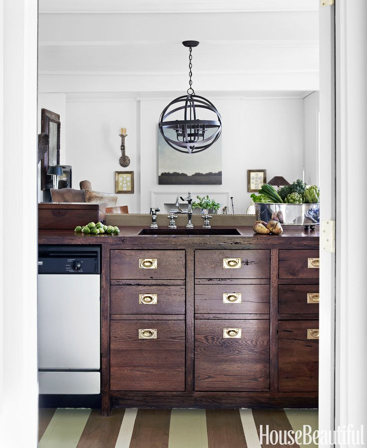 Ingram styled the kitchen to blend into the dining and living areas. He designed the oak cabinet unit (with brass hardware from Ansaldi & Sons) to look like a British campaign chest. The almost skeletal strapwork light fixture from Solaria — no glass globe, no shade — helps keep the space open.   - HouseBeautiful.com