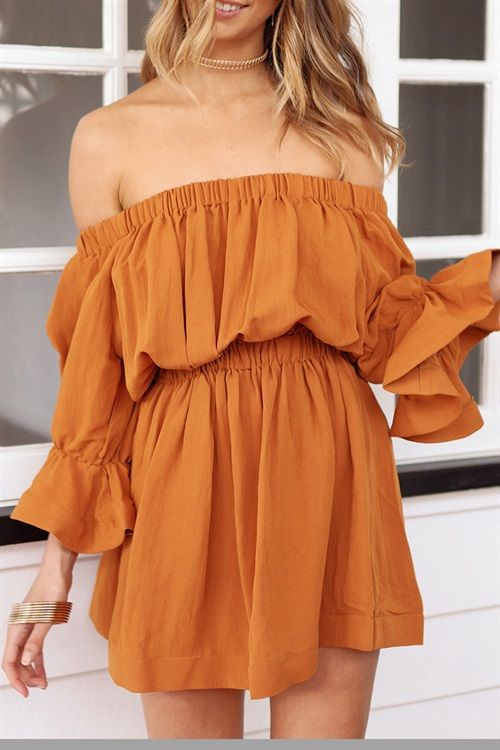 The boho style Esmerelda Dress is made from textured fabric in a burnt orange hue. It is a draping, off shoulder style and features long sleeves with a structured frill feature at the wrists and an elasticated waist band for added shape. Complete the look with tie up tan flats.