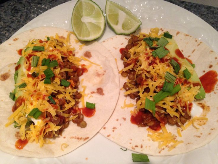 Spicy smoky lentil tacos served with avocado, cheddar cheese, hot sauce, green onions, Greek yogurt and lime wedges Full recipe :  http://chubbyvegetarian.blogspot.com/2011/04/spicy-smoky-lentil-taco-meat.html?m=1