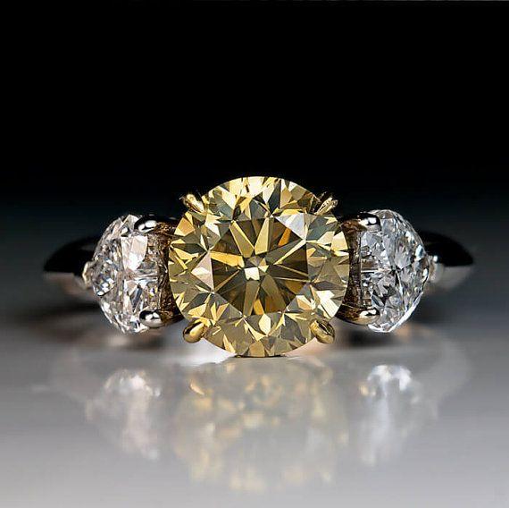 Een moderne Russische makelij 18 K geel en wit goud drie stenen verlovingsring is gecentreerd met een 2,50 ct fancy groenachtig gele ronde briljante diamant (SI2 helderheid) geflankeerd door twee lichte witte hartvormige diamant (D-E kleur, VS1 duidelijkheid, circa 0,50 ct / 1 ct totaal).  De instelling is verfraaid met 46 kleine ruitjes.  De ring is gemarkeerd met een Russische assay mark voor 750 goud (18K)  Grootte 7,75 (omvangrijke)