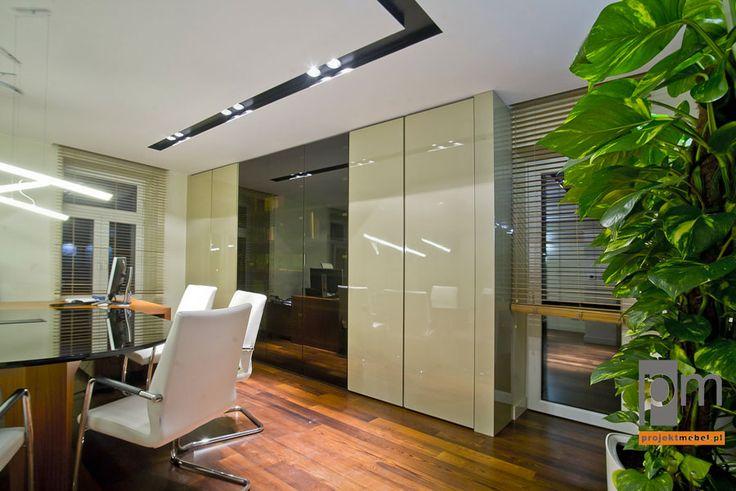 W gabinecie nie mogło zabraknąć szafy na akta. Zaproponowaliśmy mebel z wysokimi drzwiami, który mimo swoich rozmiarów nie przytłacza przestrzeni biura. Fronty szafy wykonaliśmy z lakierowanych płyt MDF, które współgrają z połyskującym blatem stołu. http://www.projektmebel.pl/realizacje/gabinety