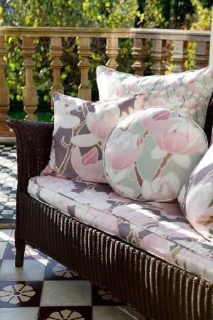 Emily Burningham -  Emily Burningham Fabric Collection - Garden sofa with cushion seat with large cream flowers and splashes of grey. Two matching cushions and cushions in floral pastel shades.