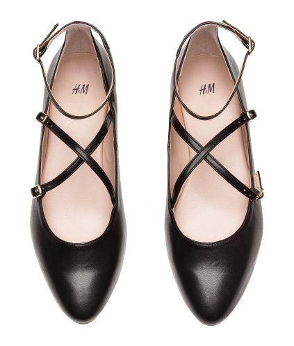 Sort. Ballerinasko i imiteret læder. Skoene har spids tå og krydsede, justerbare remme over foden og omkring anklen. For og indersål i imiteret læder. Yders