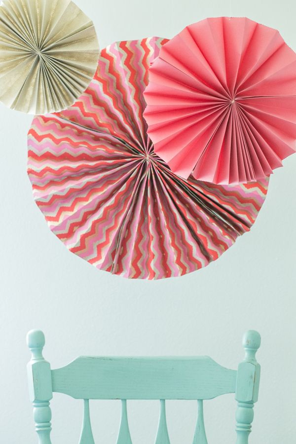 DIY giant party fans - she uses 2 sheets of rectangular paper; another post I saw used 3 sheets of square. Nice to balance the tulle poms!