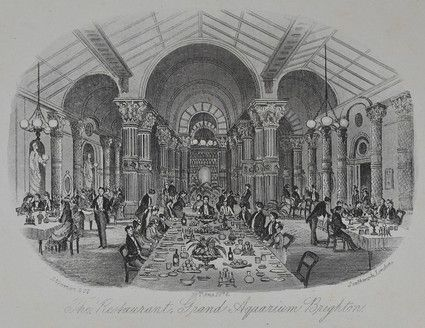 The Restaurant, Grand Aquarium, Brighton. Print by J. Newman & Co of Southwark, London. Published 19 August 1876.  The left hand wall has two alcoves with classical statues set into them. To the right are rows of dining tables,and rows of classical columns. At the far end of the room, centrally placed is a large archway flanked by columns.