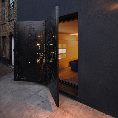 "Hidden House by Teatum+Teatum: ""..Perforated steel doors fold open  ... a glittering facade of black render and metal filings.."