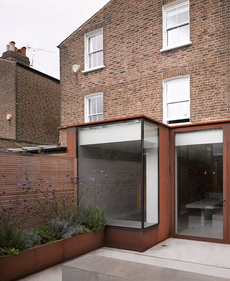 A concrete floor merges with seating inside and outside this rusted steel and glass extension to a Victorian-style house in west London