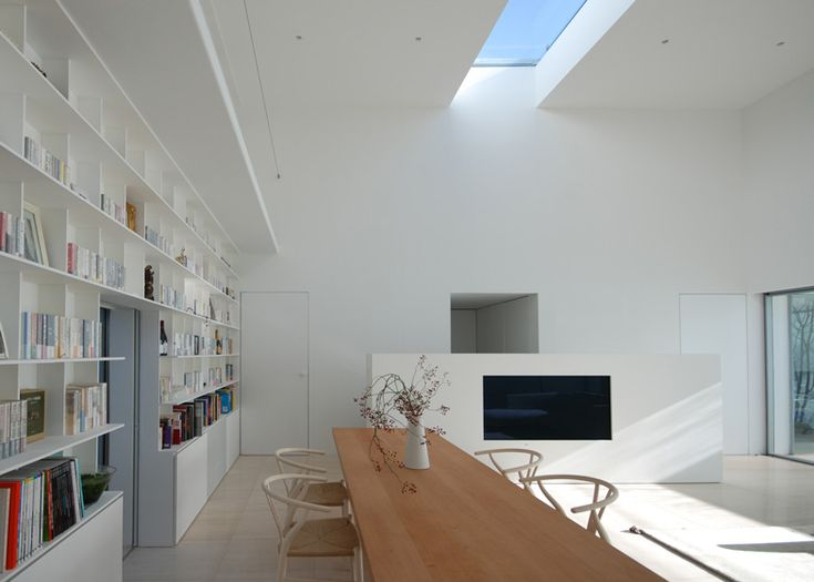 Small white house in Japan by Shinichi Ogawa & Associates with a central living and dining room with six-metre high ceilings.