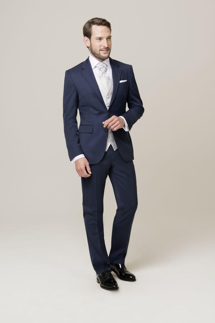 Der perfekte Hochzeitsanzug greift in der eleganten Weste die Farbe des Brautkleides auf. Komplettiert wird das festliche Outfit mit einem Plastron. Der Anzug selbst ist Schwarz, Blau oder Braun mit einem leicht glänzenden Oberstoff, der dem Ganzen eine elegante Wertigkeit verleiht.