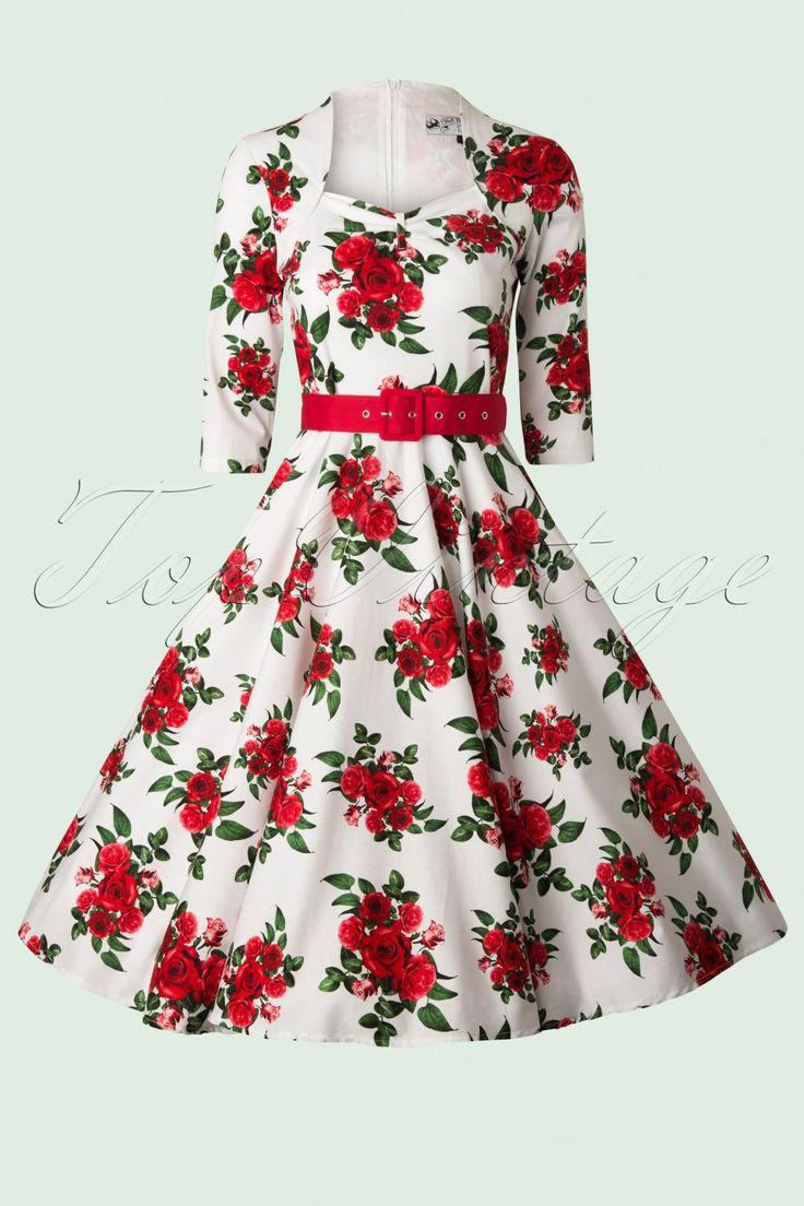 De Eternity 50s White Swing Dress Red Rosesis een prachtige 50s retro swing jurk met 3/4 mouw, ideaal voor dit seizoen!Dit elegante jurkje heeft een sierlijke hoge sweetheart halslijn met bolero effect en flatterende driekwart mouwtjes. Uitgevoerd in een fijne licht stretchende witte katoen mix met een romantische rode rozen print. Het lijfje is mooi aansluitend en looptvanaf de taille uit in een volle cirkelrok.De losse brede stoffen rode riem accentueert je taille voor een...