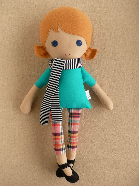 Doll: Short caramel hair in pigtails Turquoise short-sleeved top Plaid pink leggings Black ballet shoes Striped black and white stylish scarf