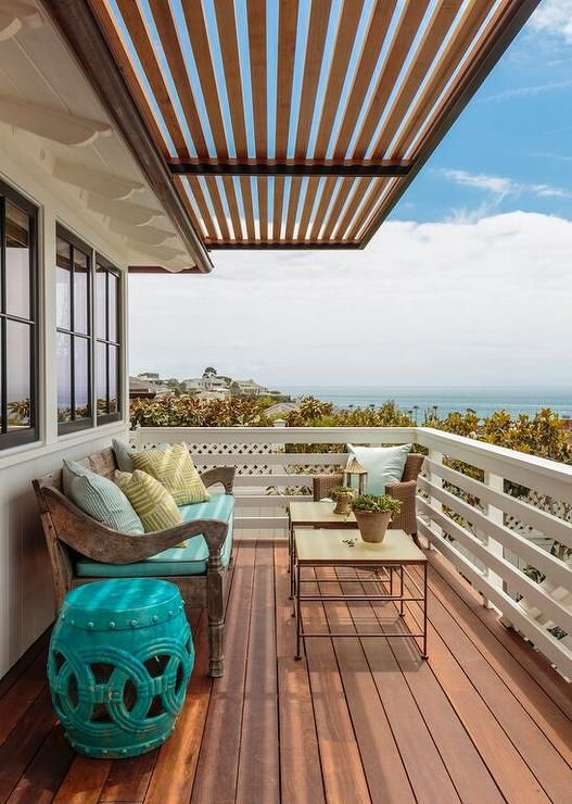 Cottage home features a second floor balcony filled with a carved wood sofa lined with a turquoise ...