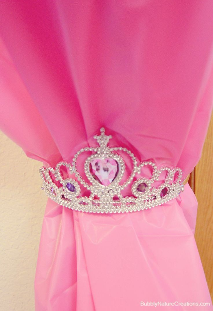 Make a curtain with pink tablecloths, then tie them back with tiaras.  Get supplies at Flower Factory - www.flowerfactory.com