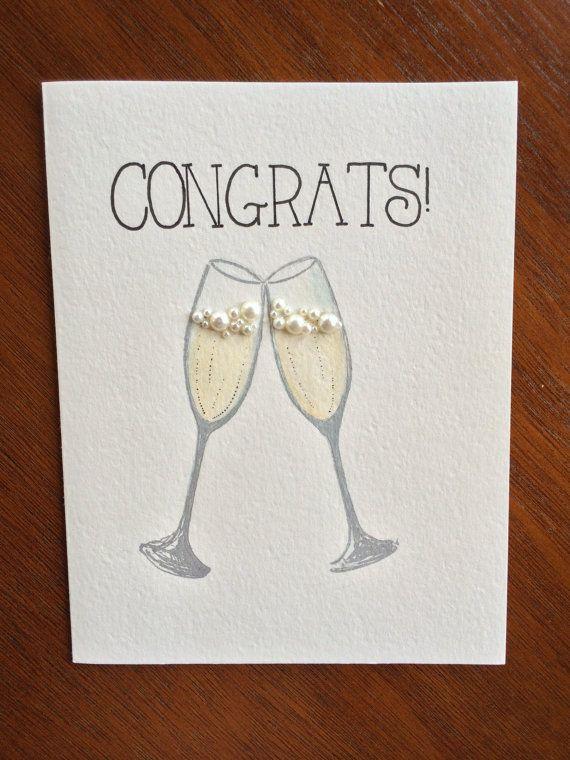 Carte de félicitations à la main et One-of-a-kind pour mariage/anniversaire/fiançailles ou n'importe quelle occasion de porter un toast à ! Design original de Fedele Deux verres à champagne argentés à la main avec des accents de perle bulle & à la main en lettres sentiment « Félicitations! » Taille : A2 (4 ¼ x 5 ½) « Luxe blanc » texturé finition vélin Enveloppe : A2 « Blanc » avec doublure d'enveloppe de paillettes argent Emballé dans un cellophane Dos : Signé et daté par l'artiste A…