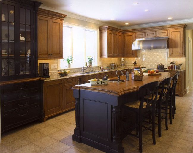 Country kitchen with black kitchen island featuring a wood countertop!