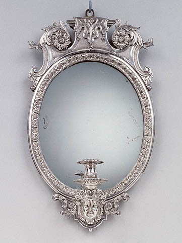 """1700 French/Swedish Wall light (one of two) at the J. Paul Getty Museum, Los Angeles - From the curators' comments: """"Acanthus leaves, a mask, and rosettes, all typical motifs of the late Baroque period, decorate this pair of oval mirrors. The mirror glass reflected the flames of the candles held in the holders, thereby increasing the amount of light produced. Small mirrored wall lights, consisting of one branch each, would probably have hung in a bedroom or study of a private townhouse."""""""