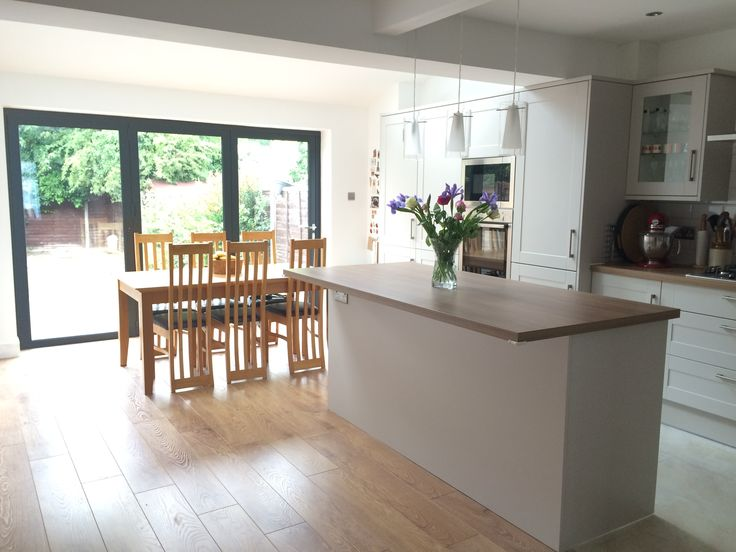 Kitchen extension with bifold doors and vaulted roof with velux windows. Family room kitchen diner with Howdens Burford Stone kitchen units with laminate flooring with mosaic transition to tile flooring.