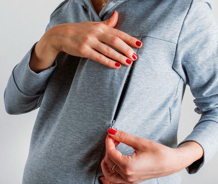 Das Umstandssweatshirt mit der Kapuze in der Farbe dunkle melange, mit Falten und Taschen. Das Sweatshirt ist elastisch und dehnbar, und das Schwangerschaftspanel verursacht, dass das Sweatshirt...