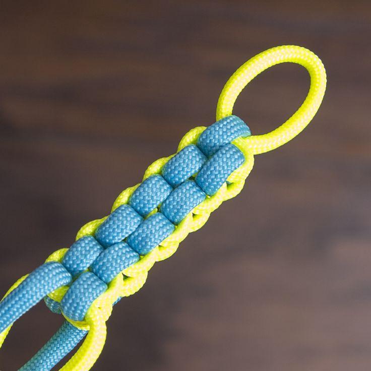 Eine Schnur wird um den Finger geschlungen und eine zweite Schnur darunter hindurch geführt und überkreuzt.    Die gelben...