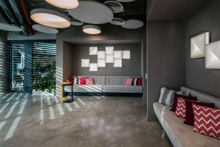Серые диваны с яркими подушками в интерьере офиса