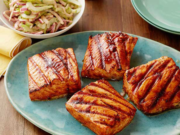 "Sweet and Spicy Grilled Salmon : The decadent-tasting ""good"" fat in salmon complements the sweet-spicy Buffalo glaze. The skin gets caramelized and crisp on the grill; it's delicious, but can be discarded to save fat and calories. via Food Network"