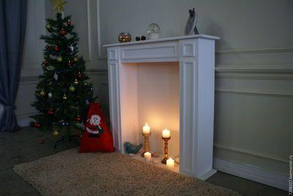 Белый декоративный камин создаст уют в рождественские и новогодние праздники. Благодаря тому, что камин высокий возможно установка в него невысоких свечей и использование из зажжеными под присмотром