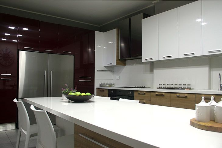 Glossy rich red cabinets wall houses the refrigerator adding spirit to this modern kitchen designed by decoaid