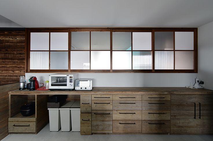 種類の違うポリカーボートネートをはめ込んだ室内窓のアイデアがユニーク。足場板の古材で造作したカウンター収納は、使い込まれた感がいい感じ。