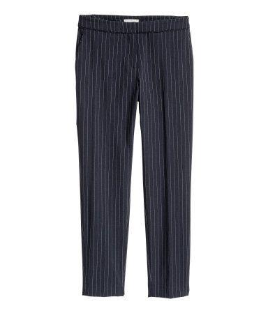 Mørk blå/Krittstripet. En dressbukse i vevd kvalitet med press. Buksen har sidelommer og passepoillommer bak. Avsmalende passform. Gylf med hempe og