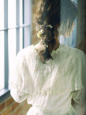 無造作に編み込んで束ねるヘアアレンジ。小さなお花を下の方に付けて大人っぽい印象に。