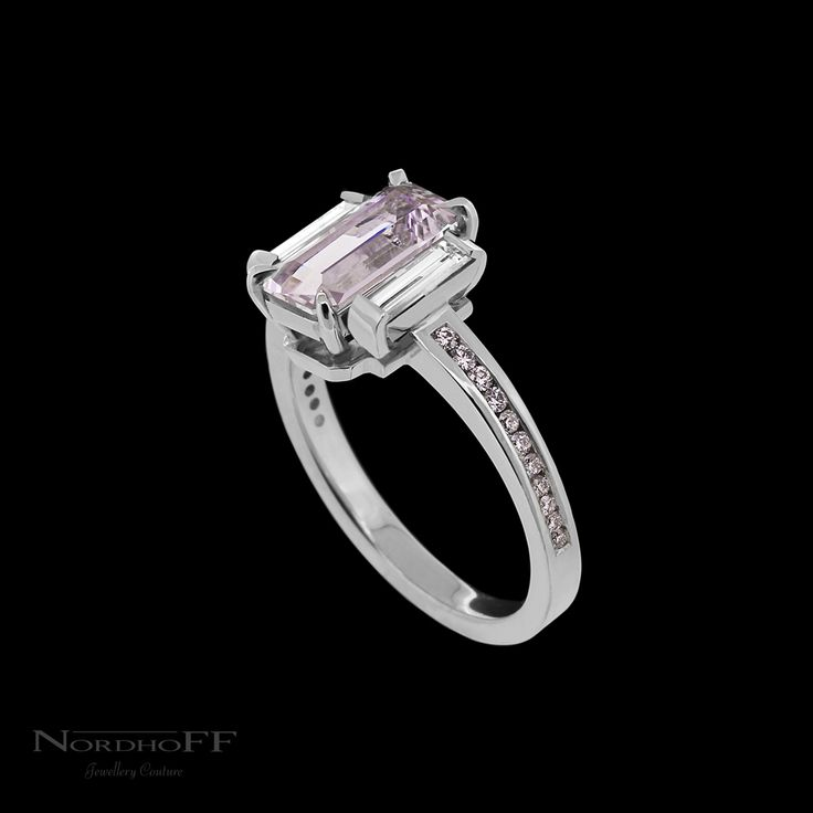 The stunning soft rose pink emerald cut sapphire sits at the centre of this handmade platinum engagement ring, carefully paired with long crisp white top grade baguette cut diamonds. The soft tones of the channel set Argyle pink diamonds match perfectly and enhance the colour of the unheated natural sapphire.