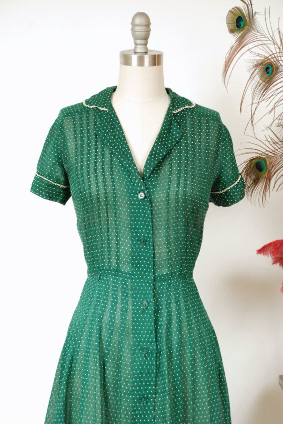 Vintage 1940s day dress in a the richest green cotton voile, with a semi-sheer weave. Its definitely sheer enough to require a slip! The entire piece is speckled with white Swiss polka dots. White lace trims the smart collar and short cuffed sleeves. The marvelous early 40s silhouette is created with pintucked darts on the bodice, and over 30 neat darts all around the top of the hips, which open to crisp, swishy pleats. This darling piece closes up the front with buttons. ✂-----Measurements…