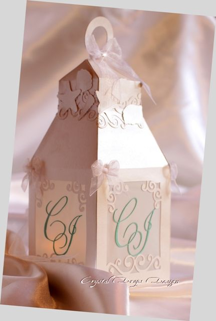 Lanterna in carta perlescente e traslucida. Con iniziali degli sposi in carta perlescente Tiffany. Rifinita con fiocchi in organza, applicazioni intagliate e Swarovski nel fiocco centrale.