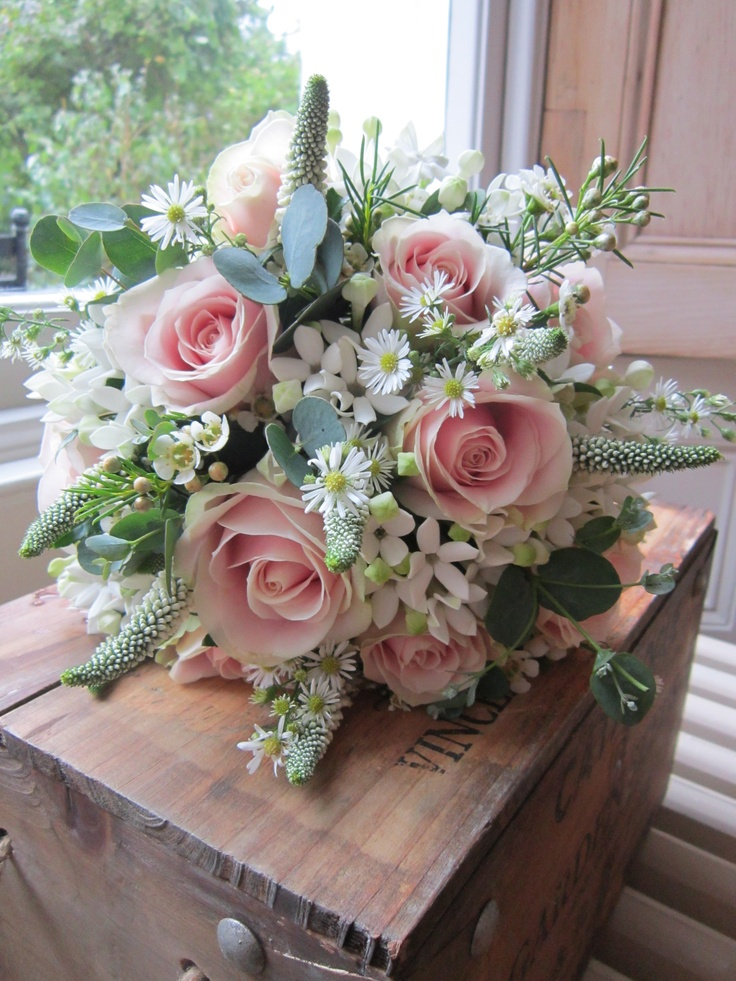 Pale pink sweet avalanche roses with white bouvardia , white veronicas , daisies and silver eucalyptus