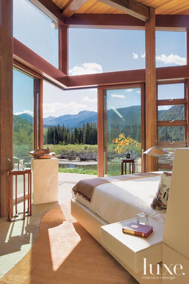 The master bedroom looks through slide-away doors from Dynamic  Architectural Windows & Doors to expansive views at an Aspen house bulit by  Jack Wilkie.