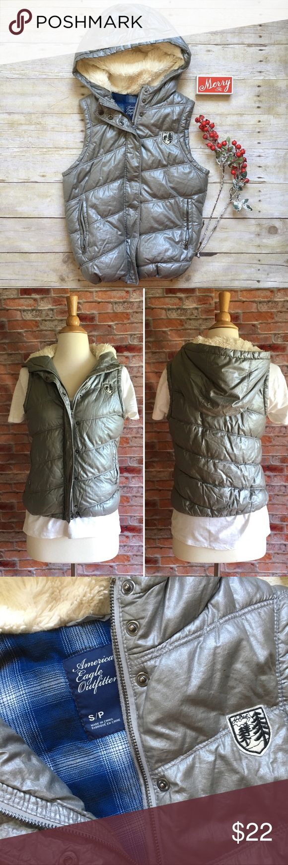 "American Eagle silver hooded puffer vest Layer this silver vest over a long sleeve tee or sweater whenever you need a little extra warmth. Zip front with snap closures. Fleece lined hood. Two front zip pockets. Elastic cinch waist. In excellent condition.  22""L.  17.5"" bust laying flat. Size small. American Eagle Outfitters Jackets & Coats Vests"