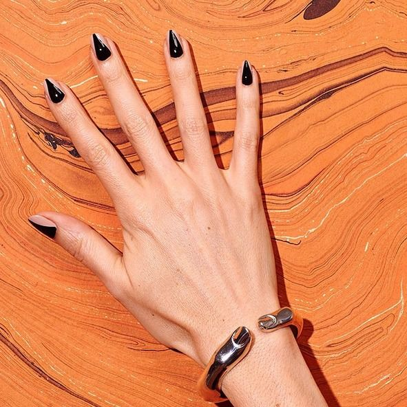 If you don't want to file your nails to sharp little points but love the creepy look of talons, try painting on a nude base color, then add a dark triangular design overtop. Instant drama (in a good way). Recreate this faux talon nail art look using essie's barely there pink 'minimalistic' and beguiling jet black 'licorice' for a super sharp mani.