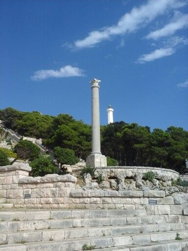 Obelisco e dietro la punta del faro di Santa Maria di Leuca