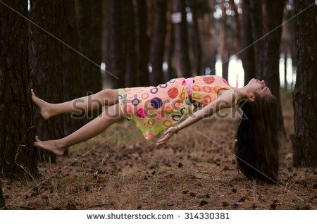 Young girl in dress levitate on the trees