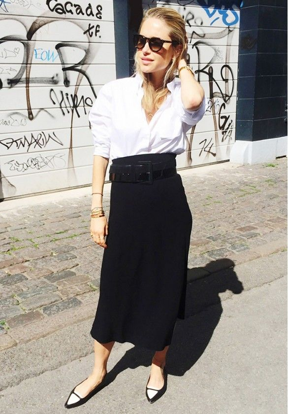 Pernille Teisbaek of Look de Pernille wears a white button-down blouse, belted midi skirt, and black and white flats