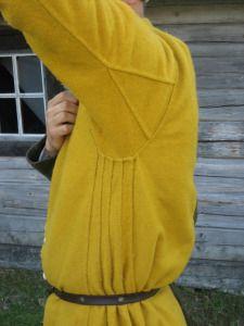 lös överkjortel med långa ärmar, ståkrage, knappar ned till midjan, sedan ihopsydd, mer än knälång.