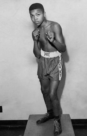 Clay poses in boxing shorts shortly after taking up the sport. Clay was introduced to boxing by policeman and boxing trainer Joe Martin in1954 after Clay, who was irate at having his bicycle stolen, had gone to the local police station and vowed to whoop whoever was responsible for the theft.