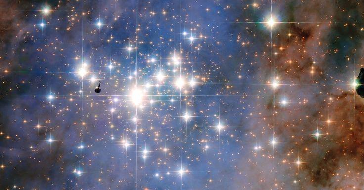 COMO UM TAPETE DE DIAMANTES - Parece uma tapeçaria feita com diamante, mas é um aglomerado de estrelas chamado de Trumpler 14, que contém algumas das mais brilhantes da Via Láctea. A região está situada a 8.000 anos-luz de distância da Terra e é uma importante zona de formação estelar. O ponto preto do lado esquerdo da imagem é a silhueta de um nódulo de gás e poeira