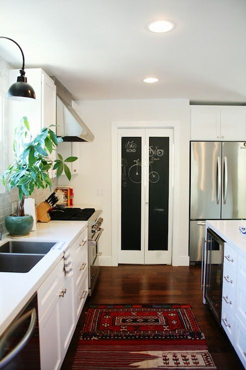 Suzie: Amber Interiors - Lovely kitchen with chalkboard bi-fold doors, white kitchen cabinets, ...