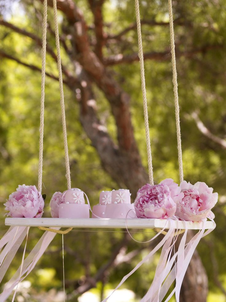 Mini cakes on a swing lovely decoration.  http://www.instyle.gr/photo-gallery/roz-vaftisi-koritsiou/
