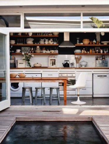 Open shelving in the kitchen. Metal stools, modern farm table. And it opens onto a pool? Sold.
