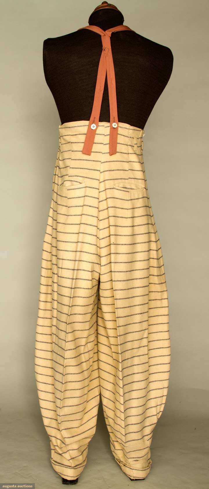 "* MAN'S WOOL ZOOT SUIT, N.J., 1938-1942 New York City 2 different pattern striped wools, long fitted coat, oversize padded shoulders & exterior pouch pockets, red plastic buttons, high-waist balloon pants, pegged cuffs, 4 slash pockets, crudely made suspenders in cinnamon wool, Sh-Sh 26"", Ch 45"", Jacket L 41"", High W (taken in) 32"", Outseam 50.5"", Inseam 31"", (large L-shaped tear near 1 pant pocket, darning on jacket's L shoulder) very good. From Newark, N.J. area"