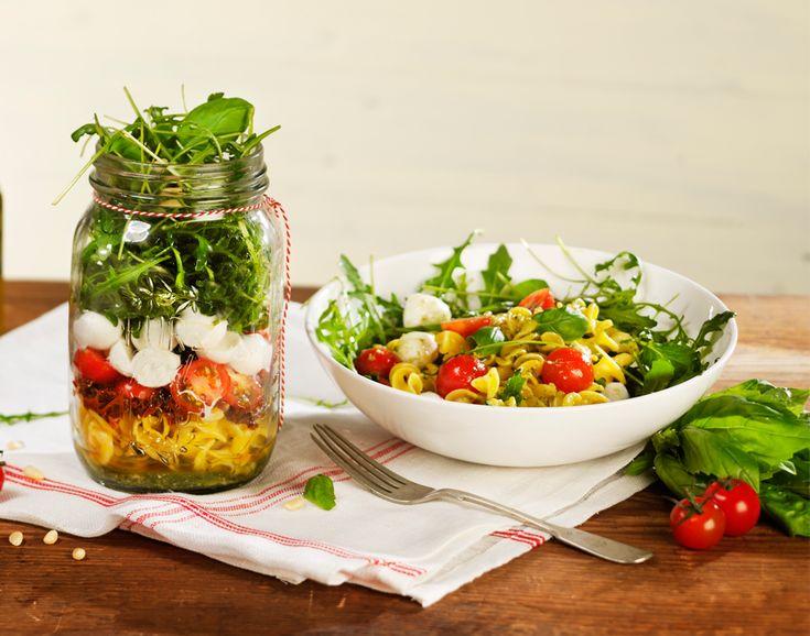 Italië in een pot! Heerlijke Italiaanse pastasalade met tomaat, mozzarella, pijnboompitjes, rucola en een verfijnde basilicum pestodressing. Als Salad in a Jar lekker en gezond voor op het werk.